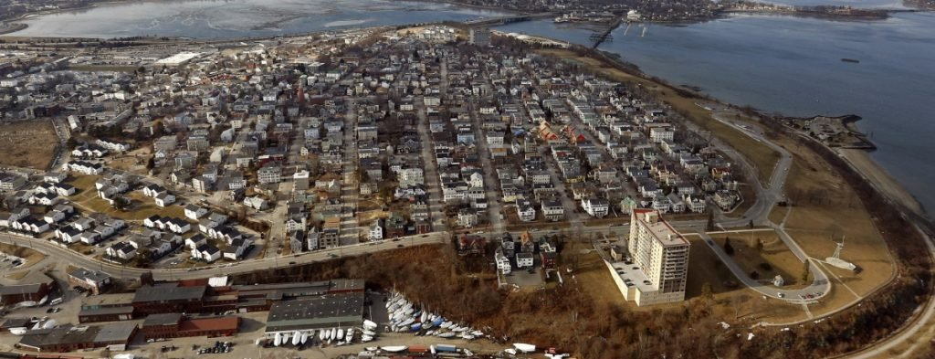 An aerial view of Munjoy Hill. The tower in the foreground is the Portland House and Fort Allen Park is at bottom right. Tukey's Bridge, which carries I-295 over Back Cove, and a disused railroad bridge are in the distance at top center.