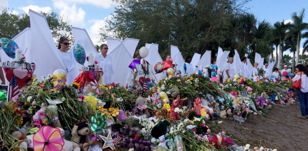 "Seventeen people dressed as angels stand Sunday at the memorial outside Marjory Stoneman Douglas High School in Parkland, Fla., for those killed in the shooting on Feb. 14. ""We want the survivors to know angels are looking over them and protecting them,"" organizer Terry Decarlo said."