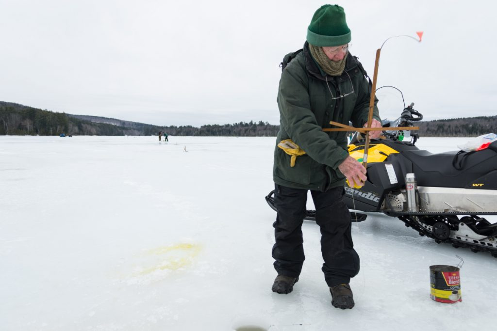 Dallas Folk, one of the organizers of Sports Unlimited of Maine, demonstrates the springing of a trap, while helping to set up for Hooked on Fishing on Berry Pond in Wayne on Sunday.