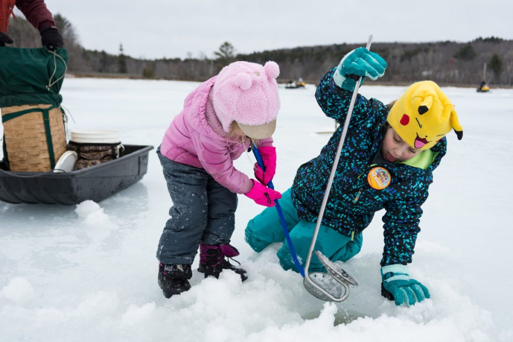 Jac-Lynne, 4, left, and Elyse Hinkley, 8, scoop ice out of a hole on Berry Pond as they take part in Hooked on Fishing in Wayne on Sunday.