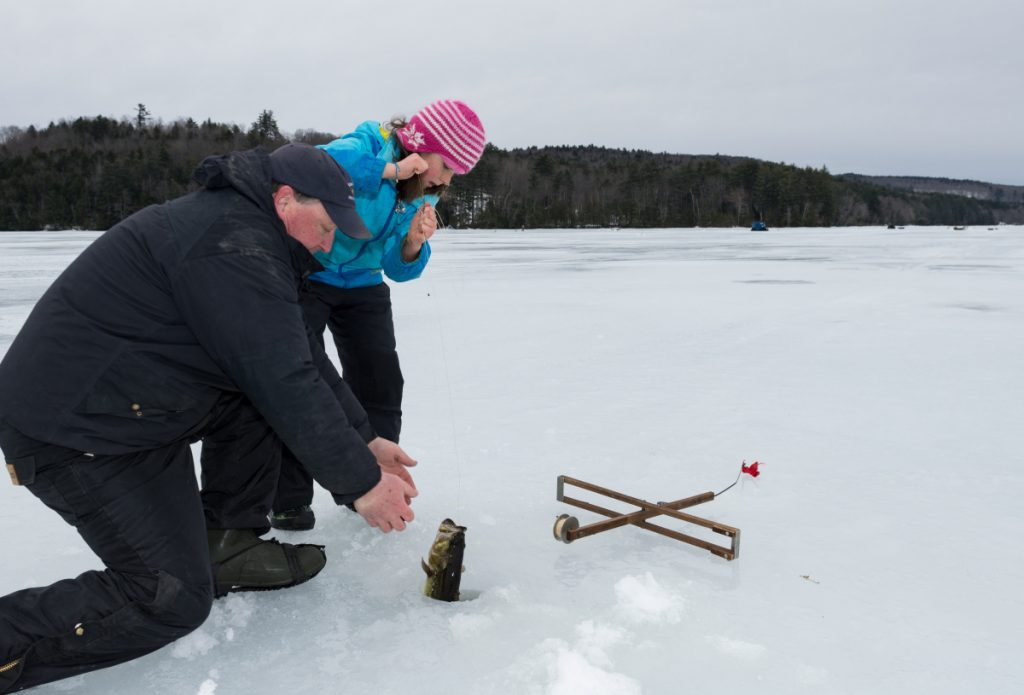 Abby St. Clair, 9, of Winthrop receives help from a family friend Sunday on Berry Pond, while pulling in a 2-pound largemouth bass. The youth fishing derby was hosted by Sports Unlimited of Maine in Wayne.
