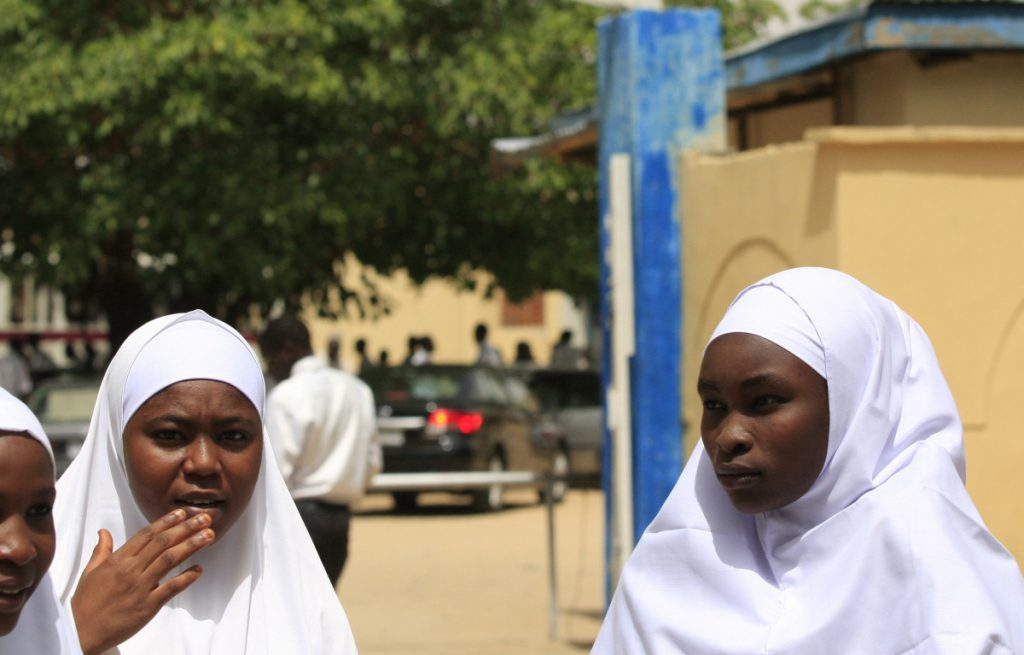 Young women stand in front of a school in Maiduguri, Nigeria.  Militants kidnapped 276 girls in 2014 from a boarding school. About 100 of those girls have never returned.
