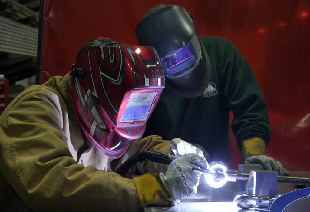 Biddeford High School student Sam Roy, 17, welds at DeepWater Buoyancy in Biddeford under the watchful eye of his mentor, Joe Woods, a welder/fabricator at the manufacturer of sub-sea buoyancy products. Last year, Roy became the first junior at the Biddeford Regional Center of Technology, which matched him with DeepWater Buoyancy, to obtain an American Welding Society certification.