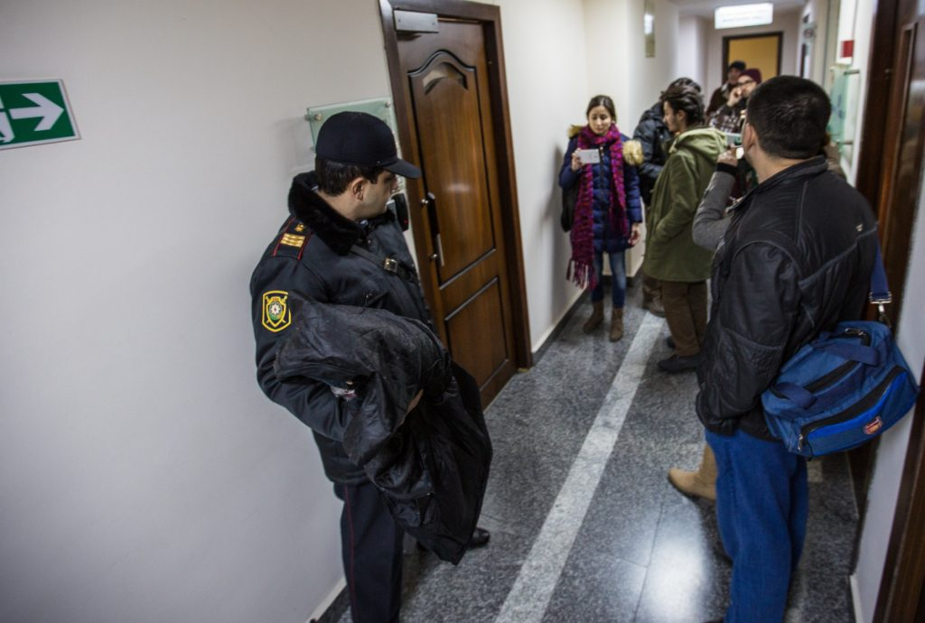 A police officer stands guard as journalists gather at Radio Free Europe's Azerbaijan bureau on Dec. 26, 2014, the day officials raided and closed the bureau. The U.S. has failed to hold the authoritarian nation accountable for its human rights violations.