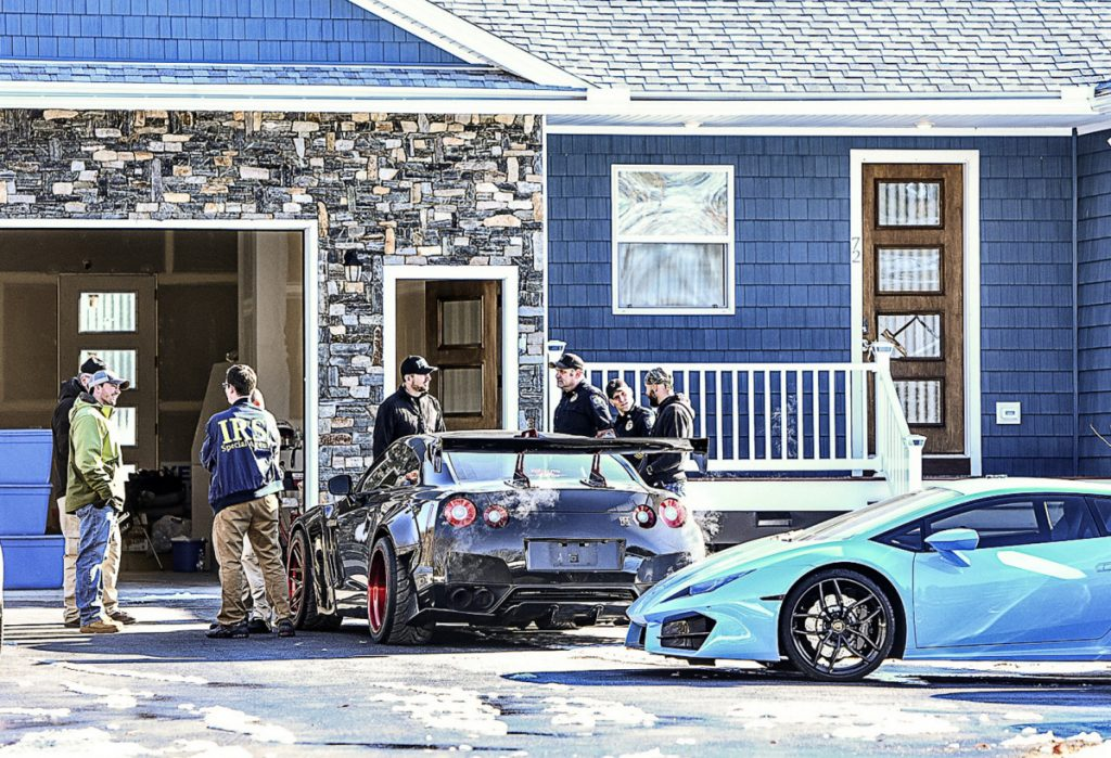 Local and federal officers search the home of Brian J. Bilodeau in Auburn Tuesday. Authorities seized several luxury cars at the house including this blue Lamborghini Huracan, valued at $190,000.