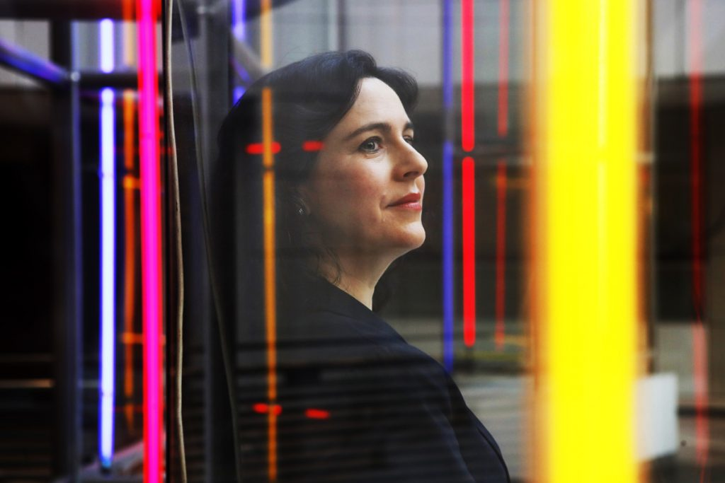 Marlene Laro, partner and COO of Potomac Law Group, is seen through a large neon sculpture at the Ronald Reagan Building and International Trade Center in Washington, where her firm has a workspace. A few law firms pioneered the virtual model in the past decade and the idea is gaining momentum, says Laro. Associated Press/Jacquelyn Martin