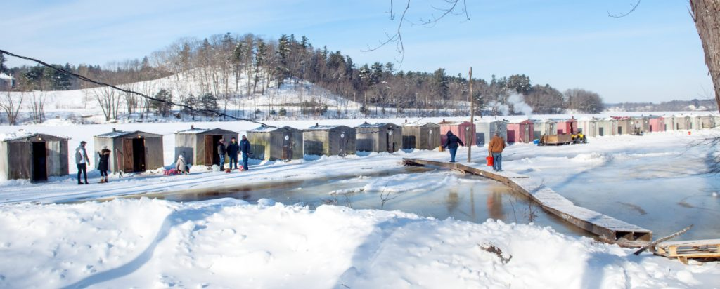 People walk across a bridge and onto the frozen Kennebec River on Dec. 30, 2017, at Baker Brothers Smelt Camps in Pittston. Baker's is putting its camps away Sunday, three days ahead of an expected arrival of U.S. Coast Guard icebreakers.