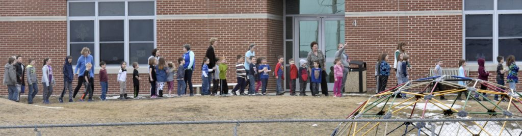 Students in the early grades stand outside the Mount View school complex in Thorndike after being evacuated because of a suspected chemical release Wednesday. Apparently a student released pepper spray in a classroom, affecting about 20 students.