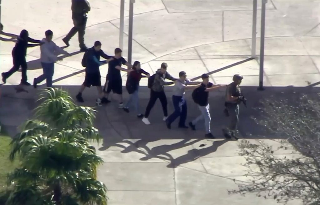 In this image from video, students from the Marjory Stoneman Douglas High School in Parkland, Fla., evacuate the school after the shootings on Feb. 14.