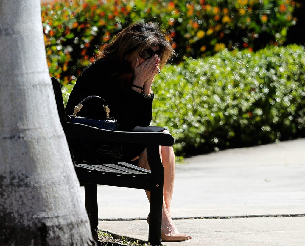 A woman weeps as she sits outside the Temple K'ol Tikvah before the funeral of Meadow Pollack, a victim of the Wednesday shooting at Marjory Stoneman Douglas High School, in Parkland, Fla., on Friday. Nikolas Cruz, a former student, was charged with 17 counts of premeditated murder.