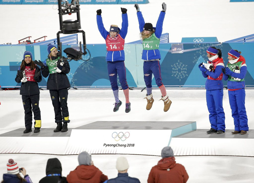 Gold medalists Kikkan Randall and Jessica Diggins of the United States are  flanked by silver winners Stina Nilsson and Charlotte Kalla of Sweden, left, and bronze medalists Marit Bjoergen and Maiken Caspersen Falla of Norway after the women's team sprint freestyle cross-country  final at the 2018 Winter Olympics.