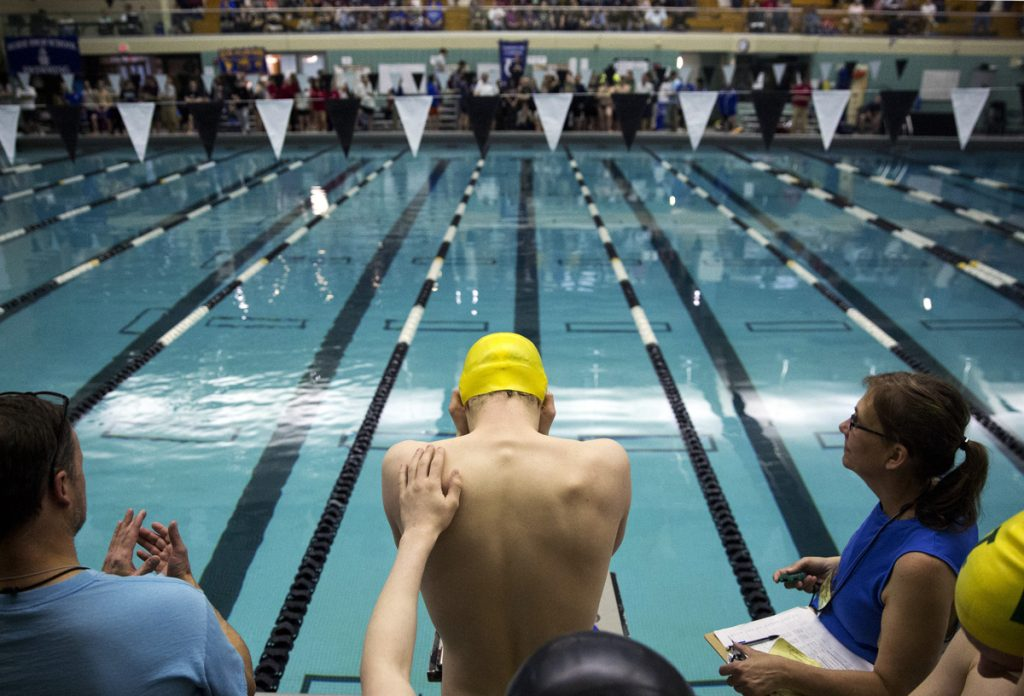 A teammate gives Liam Sullivan, a junior from Mount Desert Island, a reassuring pat on the back before he starts in the 400-year freestyle relay, the last event of the Boys Class B state swimming and diving championship. MDI's second place finish  allowed them to take home the state championship trophy. Sullivan set a meet record in the 200-yard individual medley and another in the 100 backstroke.