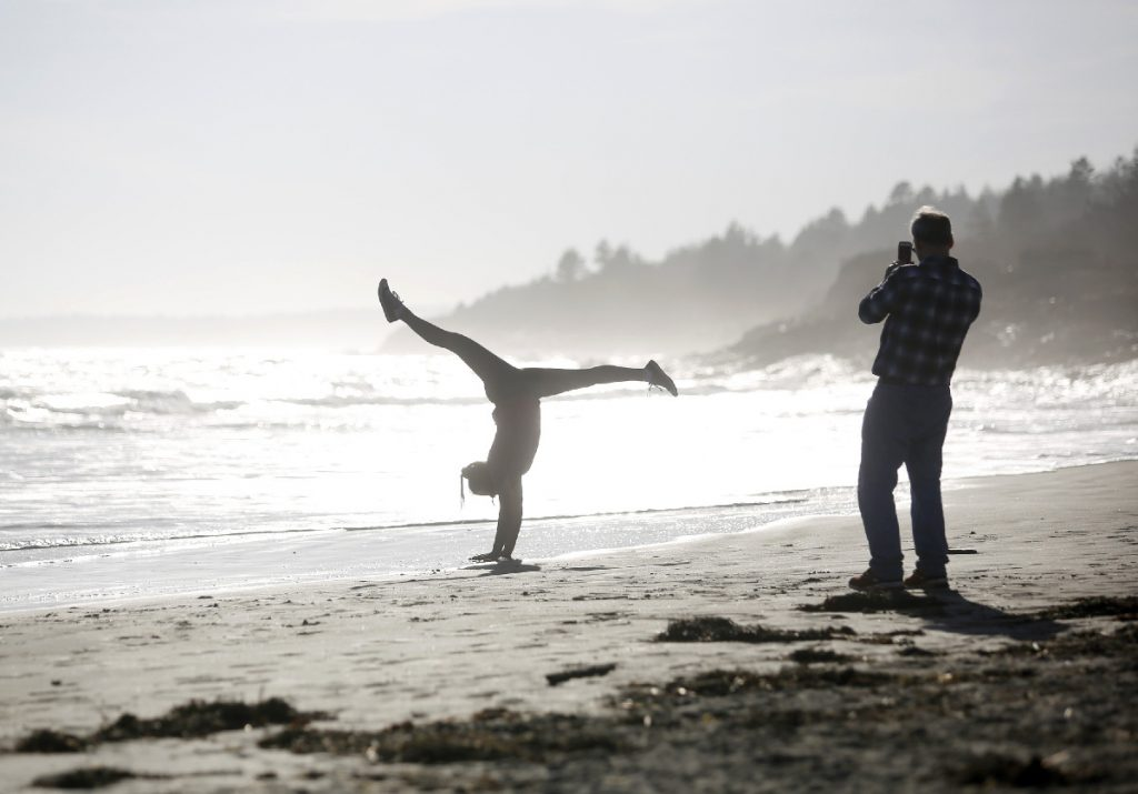 Michael Malone of South Portland takes pictures of his daughter Anna, 15, as she does handstands at Higgins Beach on Wednesday, Feb. 21, 2018.The temperature reached 68 degrees on Wednesday and set a Maine record for the warmest day in February. Staff photo by Derek Davis