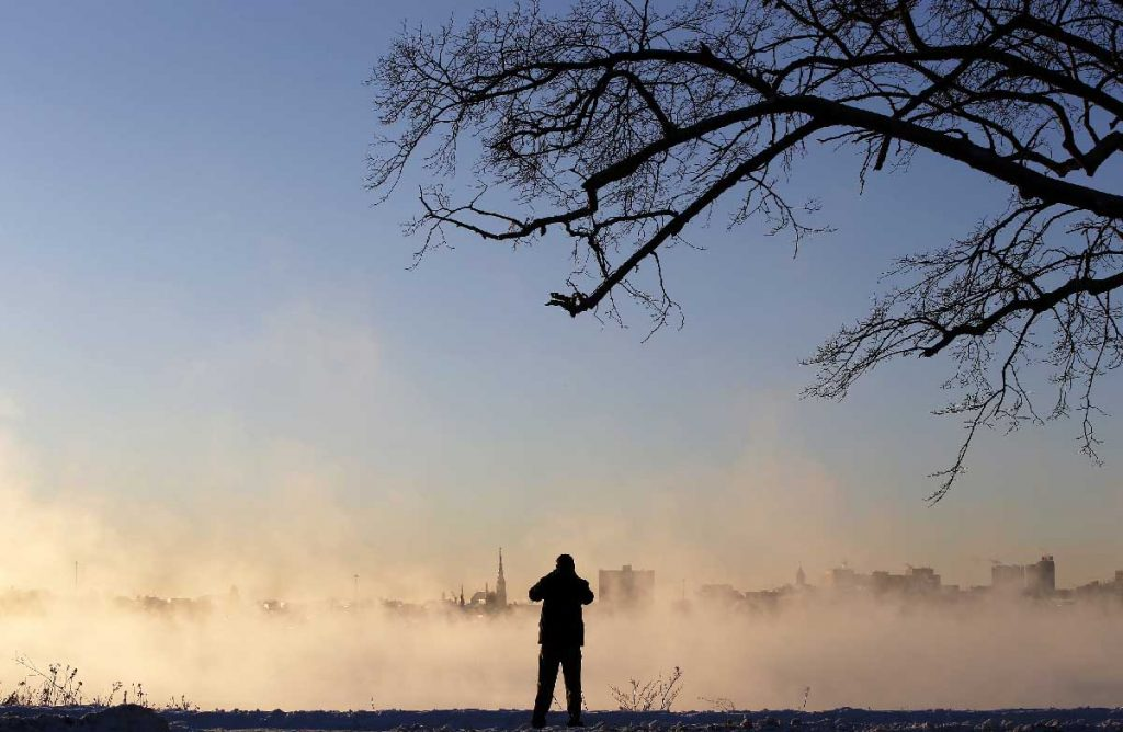 "Todd Chase of Gorham takes photos of the city skyline emerging from sea smoke over Back Cove at sunrise during single-digit weather on Tuesday, January 2, 2018. Chase said he frequently pulls over to take photos during his commute. ""I like to snap a shot every time I see something unusual,"" he said. ""This is one of those mornings."" Staff photo by Ben McCanna"