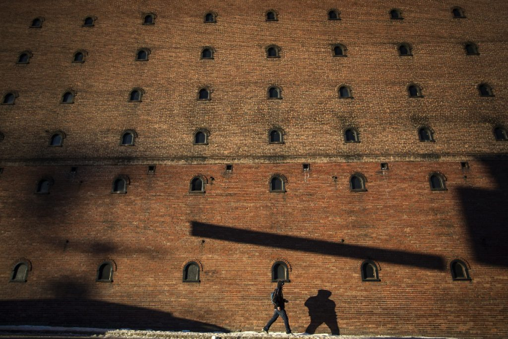 BIDDEFORD, ME - JANUARY 25: A pedestrian casts a shadow on the wall of an old textile mill on Jan. 25, 2018, as he walks along Main Street in Biddeford. Staff photo by Derek Davis