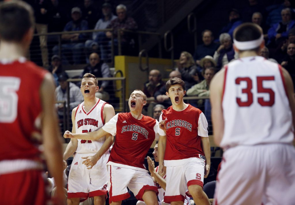 Scarborough vs South Portland Class AA South final. Scarborough teammates Zoltan Panyi, left, Alexander Austin and Sam Gorey celebrate from the bench after Nicholas Fiorillo scored in the fourth quarter of the Class AA South regional basketball final. Staff photo by Derek Davis