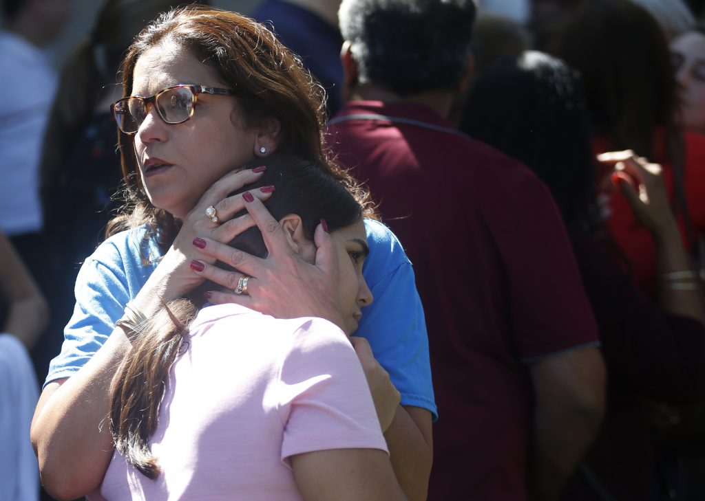 Mourners comfort each other Thursday at a prayer vigil at the Parkland (Fla.) Baptist Church for the victims of the shooting at Marjory Stoneman Douglas High School. Readers say it's past time to take action that will prevent such school shootings.
