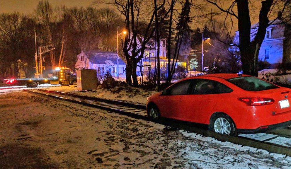 A tow truck arrives to remove a car stuck on the tracks in Portland's Woodfords neighborhood.