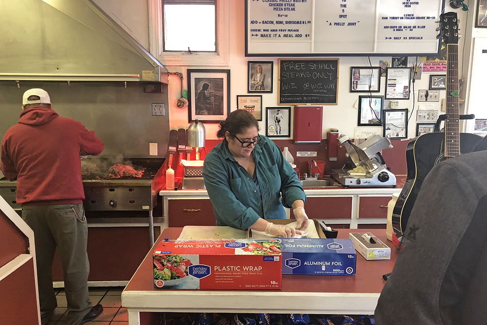 While Keith Costello slices  steak on the grill at the 5 Spot, wife and co-owner Rosetta iannaccone hands out cheesesteaks wrapped in foil Monday.