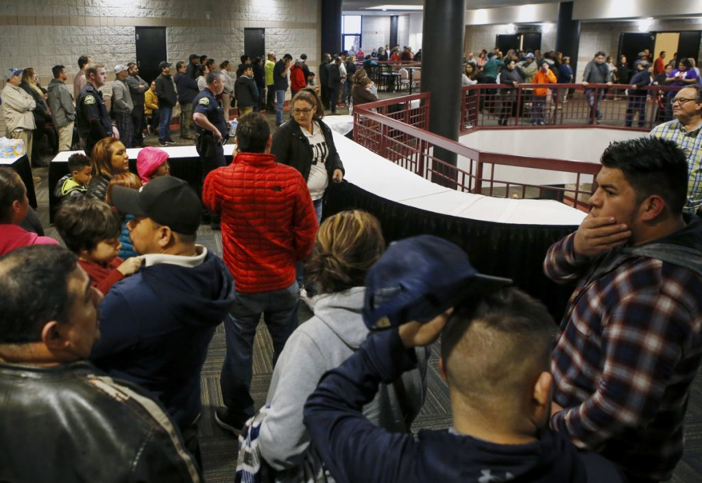 People line up inside the Dalton Convention Center to pick up their children on Wednesday in Dalton, Ga. Students from Dalton High School were evacuated to the convention center after social studies teacher Jesse Randal Davidson barricaded himself in a classroom and fired a handgun, authorities said.