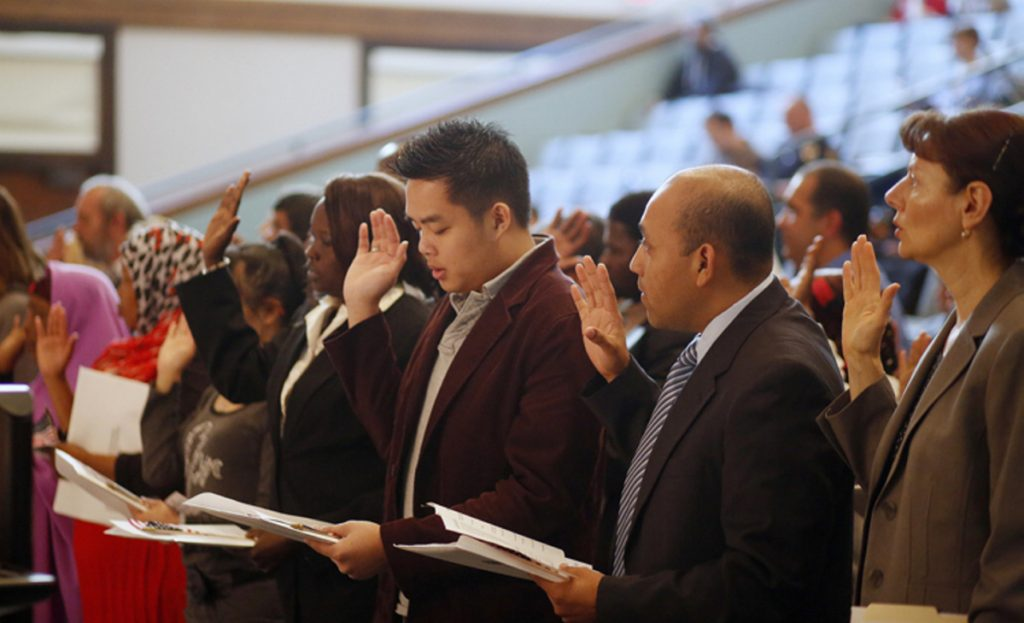 New U.S. citizens are naturalized in a 2013 ceremony in Portland. A reader says immigrants are better off if they work their way to success instead of getting help.