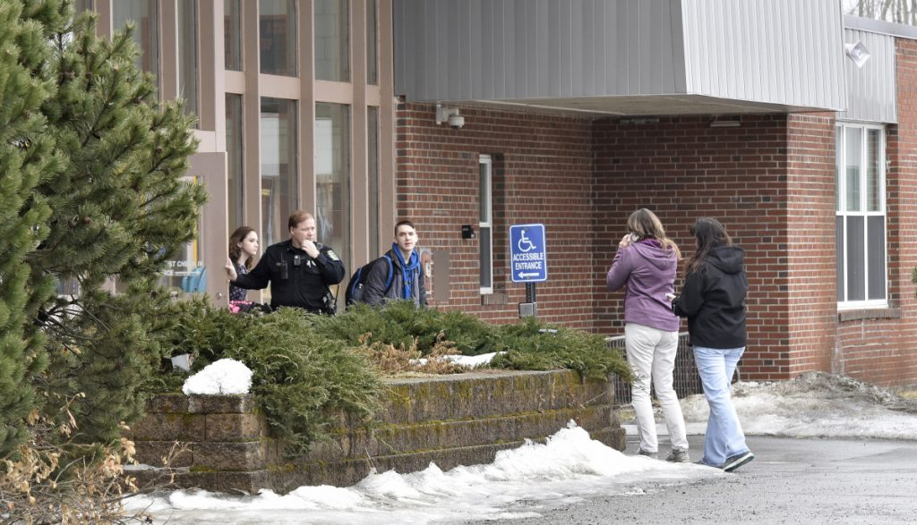SAD 54 School Resource Officer David Daigneault speaks with parents as students exit Skowhegan Area High School during a lockout after a threat made Thursday. It was the second threat there this week. Students were allowed to leave the school, but no one was allowed to enter.