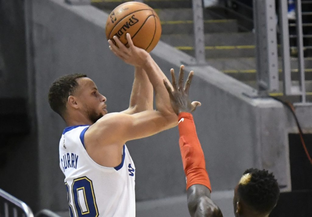 Warriors guard Stephen Curry shoots from the 3-point line as Hawks guard Dennis Schroder defends during the Golden State's 114-109 win in Atlanta on Friday. Curry scored 28 points but left the game in the third quarter.