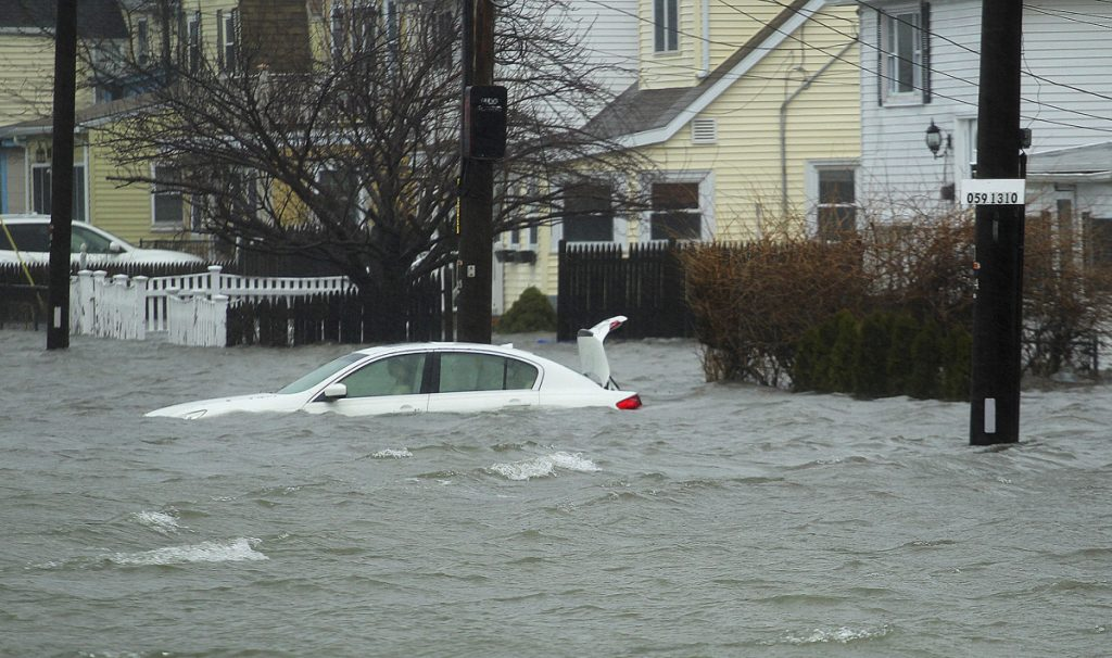 A car along Sea Street is under several feet of water during the storm Friday in Quincy, Mass. A relentless storm pounded the Atlantic coast with hurricane-force winds and sideways-blown rain and snow Friday from North Carolina to Maine.