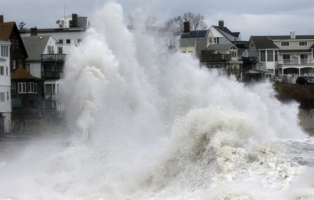 A large wave crashes into a seawall in Winthrop, Mass., Saturday, a day after a nor'easter pounded the coast.