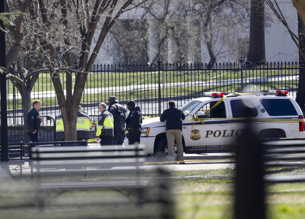 Law enforcement officers gather in front of the White House in Washington on Saturday after a man shot himself outside the building.