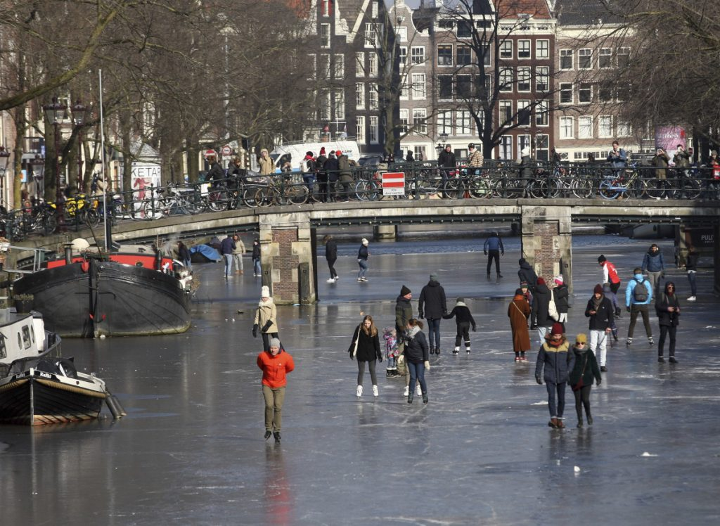 People walk and skate on the frozen Prinsengracht canal in downtown Amsterdam on Friday as cold weather gripping much of Europe hangs on.