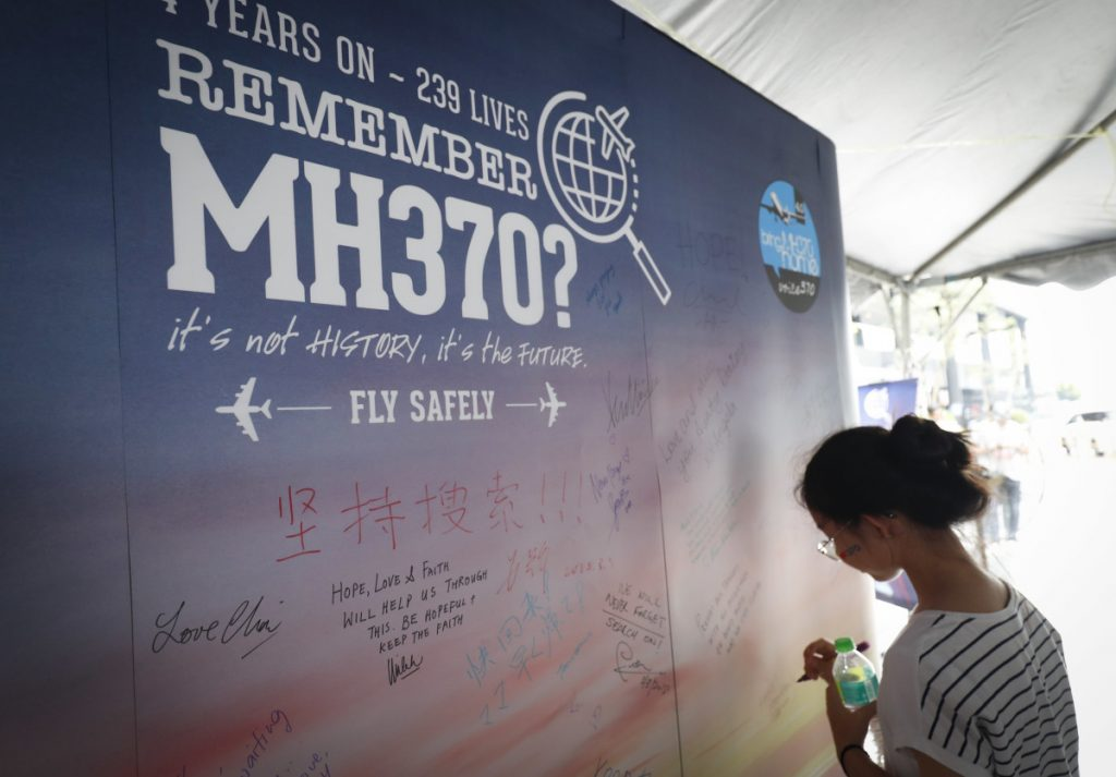 A girl writes a condolence message during the Day of Remembrance for MH370 event in Kuala Lumpur, Malaysia, on Saturday. The remembrance event marked the fourth anniversary of the jet's March 8, 2014, disappearance.