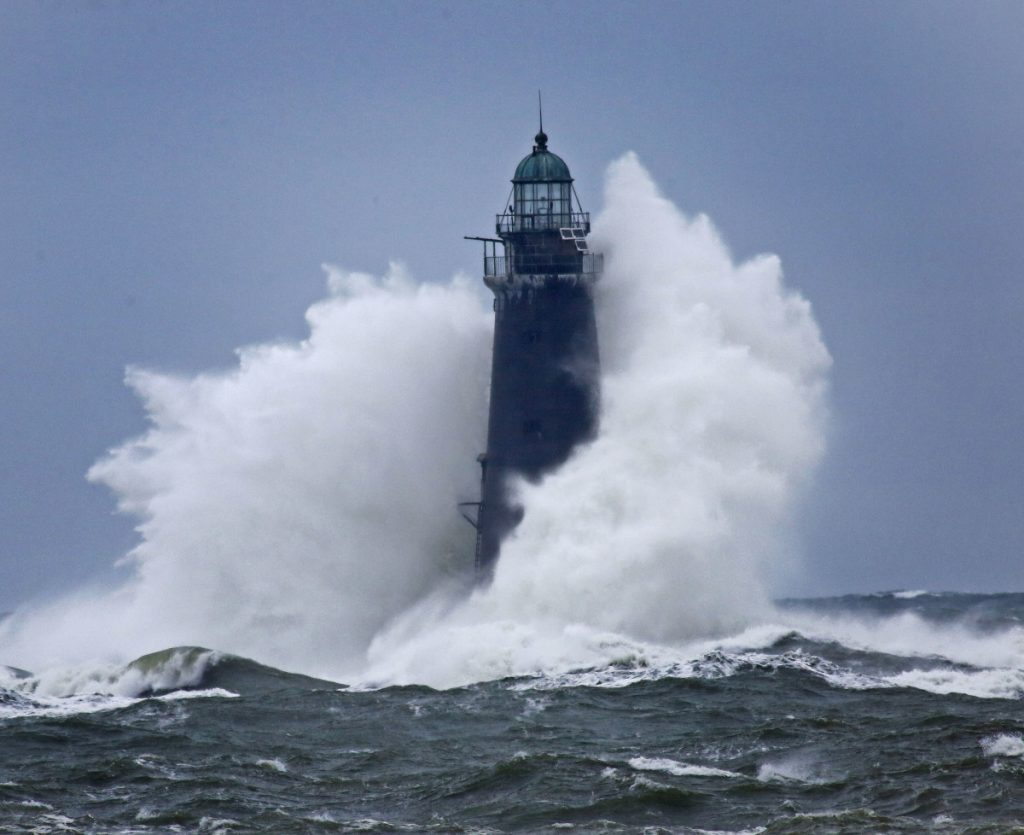 Waves crash against Minot Light off Scituate, Mass., on Sunday as winds continued to batter the coast. The 89-foot-tall lighthouse was built in 1855.