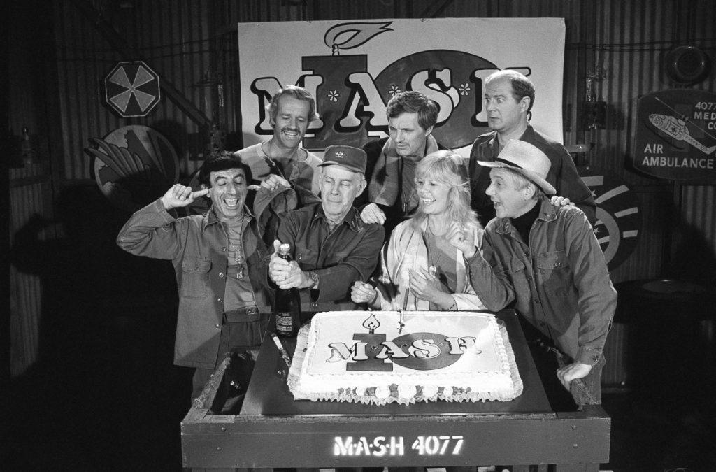 "Jamie Farr, from front left, plugs his ears as cast members of the ""M.A.S.H"" television series Harry Morgan, Loretta Swit, William Christopher and, in back from left, Mike Farrell, Alan Alda and David Ogden Stiers celebrate during a party on the set of the popular CBS program in Los Angeles. Stiers, a prolific actor best known for playing Maj. Charles Winchester, has died at 75."