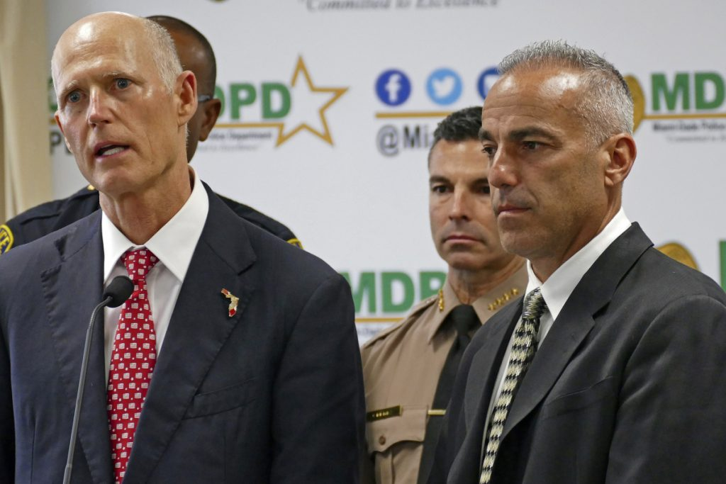 Florida Gov. Rick Scott talks alongside Andrew Pollack, right, whose daughter Meadow was murdered in Parkland, during a news conference in Doral, Fla., on Feb. 27.