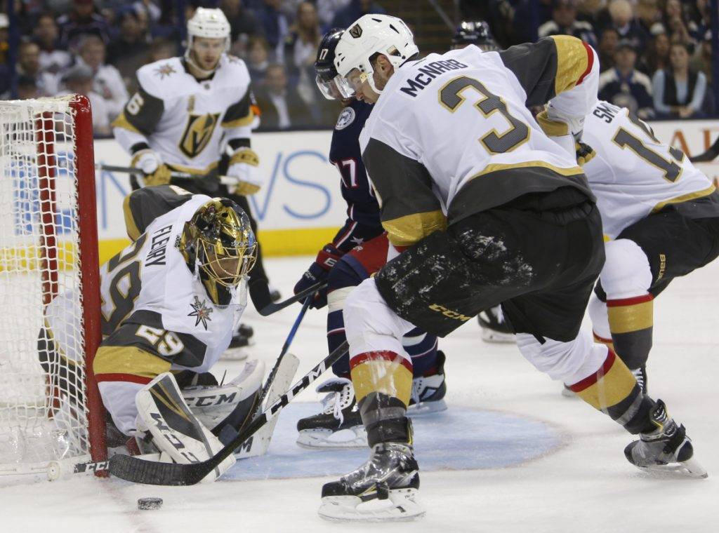 Vegas goalie Marc-Andre Fleury makes a save as Brayden McNabb, right, and Columbus' Brandon Dubinsky look for a rebound during the second period Tuesday night in Columbus, Ohio. Columbus won 4-1.
