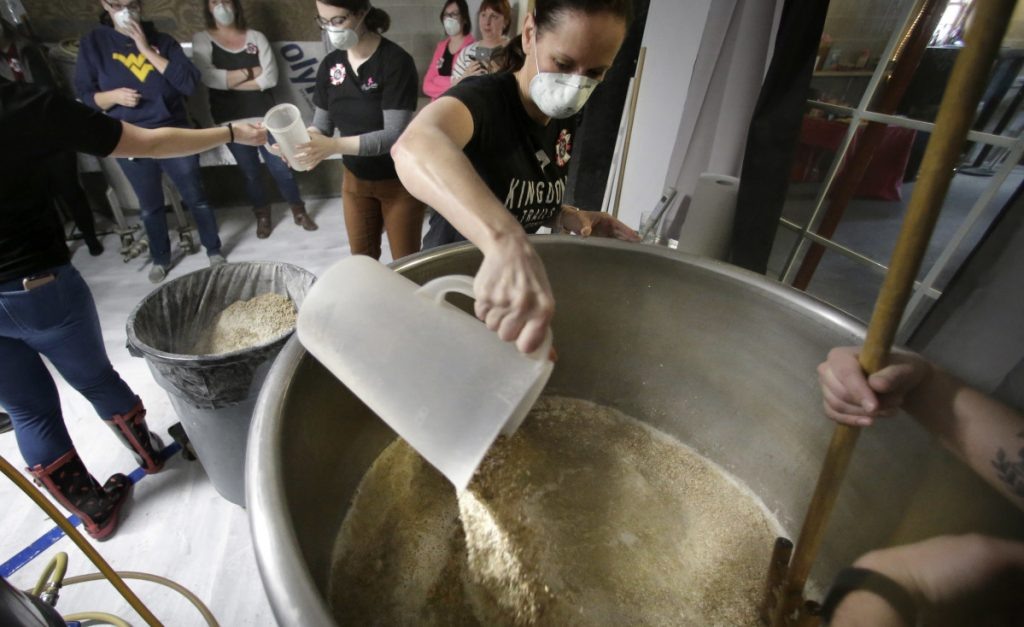 Elizabeth Bove, of Woodstock, Conn., pours grain into a mash mixture at Black Pond Brews brewery in Danielson, Conn.