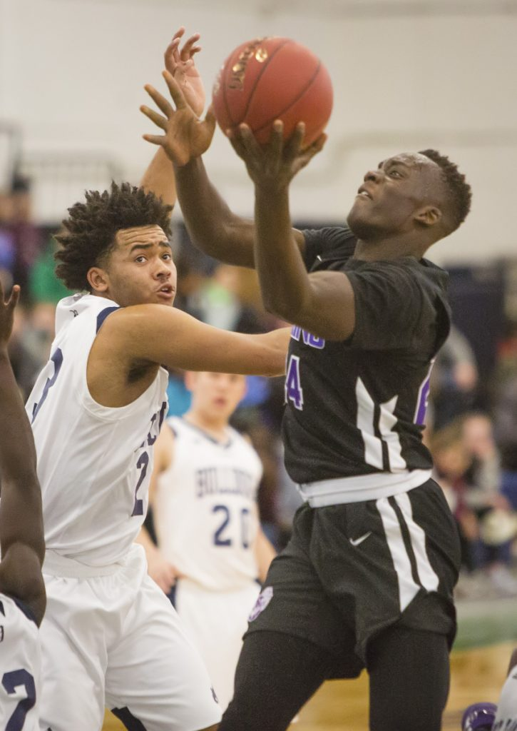 PORTLAND, ME - DECEMBER 28: Deering's Ben Onek drives t the basket as Portland's Trev Ballew tries unsuccessfully to defend him during Boys varsity basketball action during the Christmas tournament at the Portland Expo on Thursday, December 28, 2017. (Staff Photo by Carl D. Walsh/Staff Photographer)