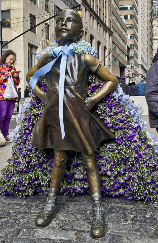 "The ""Fearless Girl"" statue wears a cape of flowers to mark International Women's Day on Thursday."