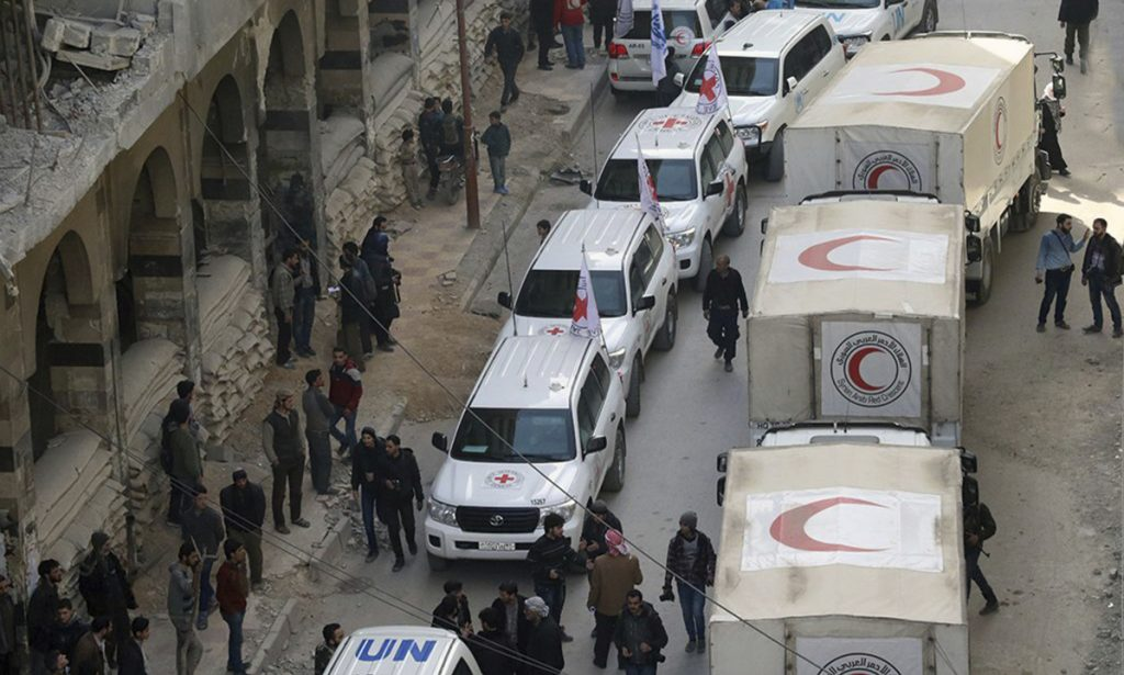 Civilians gather near a convoy of relief vehicles in Douma, eastern Ghouta, a suburb of Damascus, Syria, on Monday. A second convoy has been delayed.