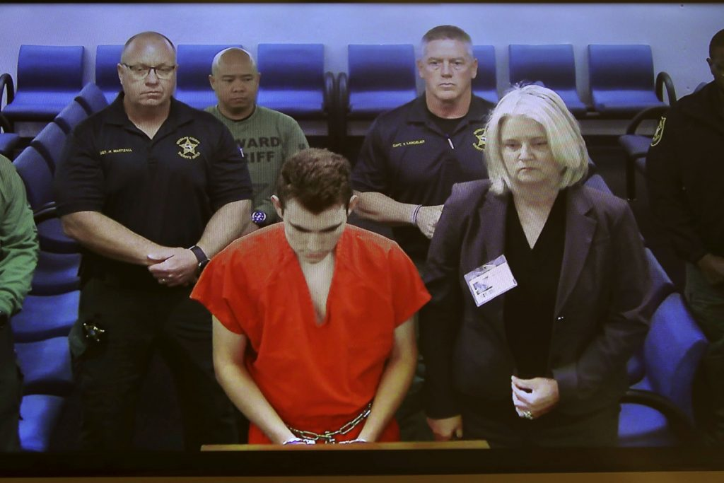 In this image taken from a video monitor, Nikolas Cruz, a former student accused of opening fire at Marjory Stoneman Douglas High School on Feb. 14, appears in magistrate court via video conference from jail on Friday for his initial appearance on attempted murder charges that were added by a grand jury, in Fort Lauderdale, Fla.