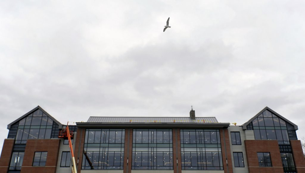 A seagull flies past the University of New England's newly dedicated student commons. The Danielle N. Ripich Commons features bird-proof glass to prevent collisions as birds migrate down the nearby Saco River.