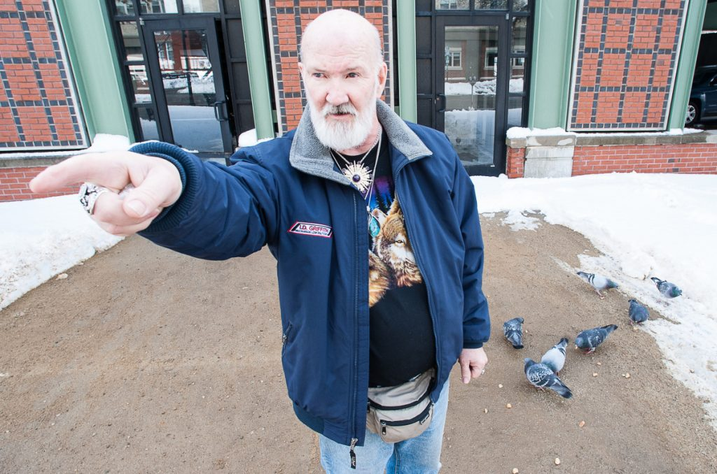 David Sites points to Oak Park Apartments in Lewiston, where he lives, as birds feed on bread he has just thrown down for them. Despite a threat of eviction for feeding the birds, Sites plans to continue feeding the pigeons, as he has done for the past 10 years. Visit sunjournal.com to watch a video of Sites feeding the birds and explaining why he plans to continue. (Russ Dillingham/Sun Journal)