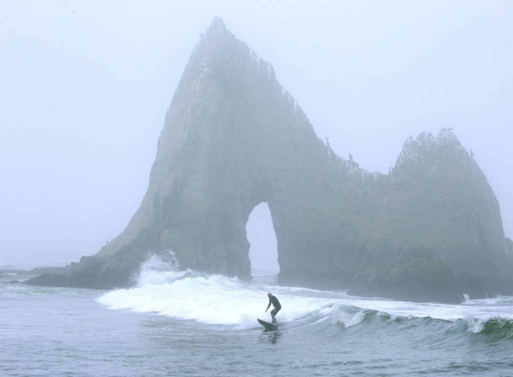 A surfer rides a wave in front of Shark Tooth Rock at Martins Beach in Half Moon Bay, Calif. The beach has become a legal battle between Vinod Khosla and the public.
