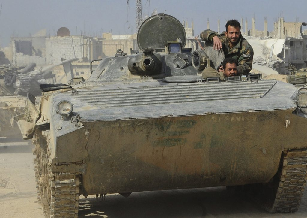 Syrian government soldiers ride in their armored vehicle during a battle against Syrian rebels in eastern Ghouta.