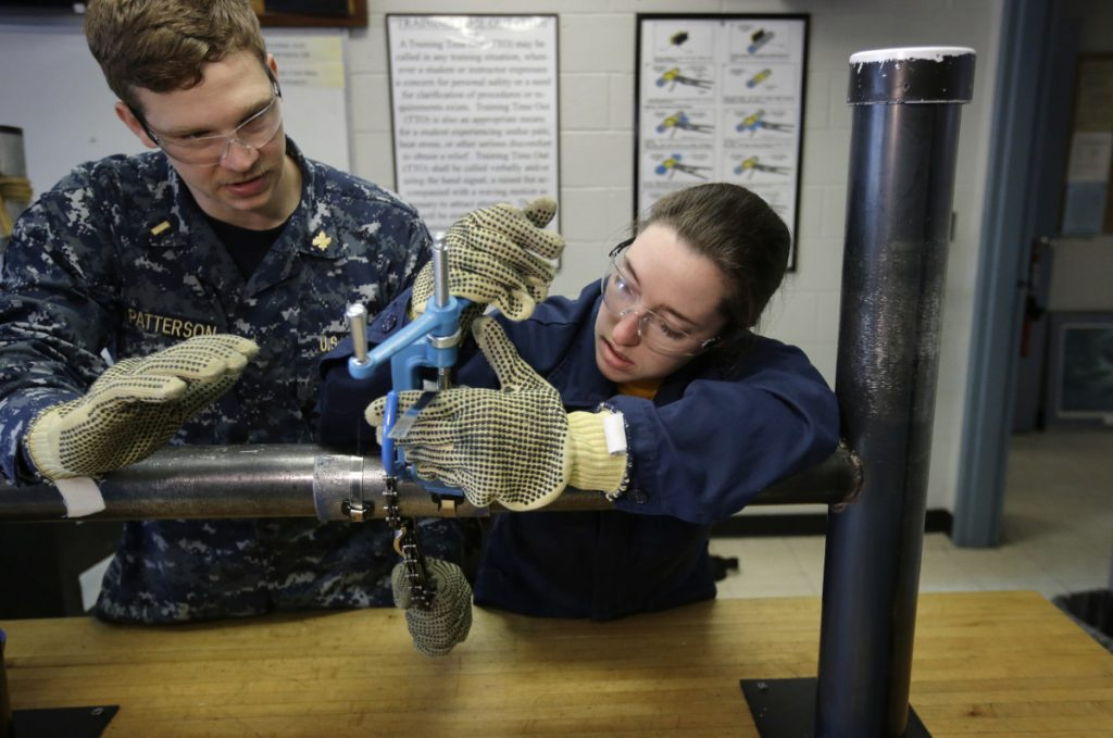 Navy Ensigns Thomas Patterson of Anaheim, Calif., and Megan Stevenson of Raymond, Maine, train to patch pipe leaks last year at the Naval Submarine School in Groton, Conn.
