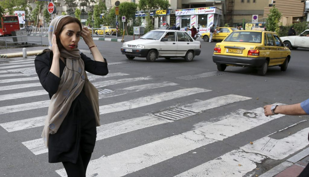An Iranian woman adjusts her head scarf while crossing a street in Tehran, Iran, in 2016 shortly after officials announced the deployment of 7,000 male and female officers to police the government-mandated dress code.