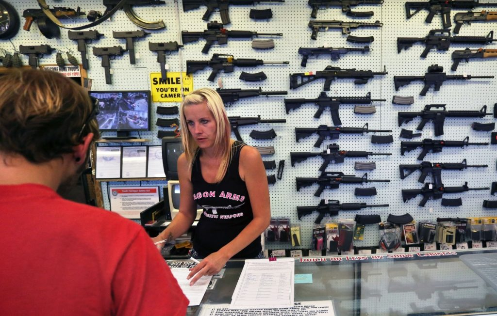 With guns displayed for sale behind her, a gun store employee helps a customer at Dragonman's, east of Colorado Springs, Colo.