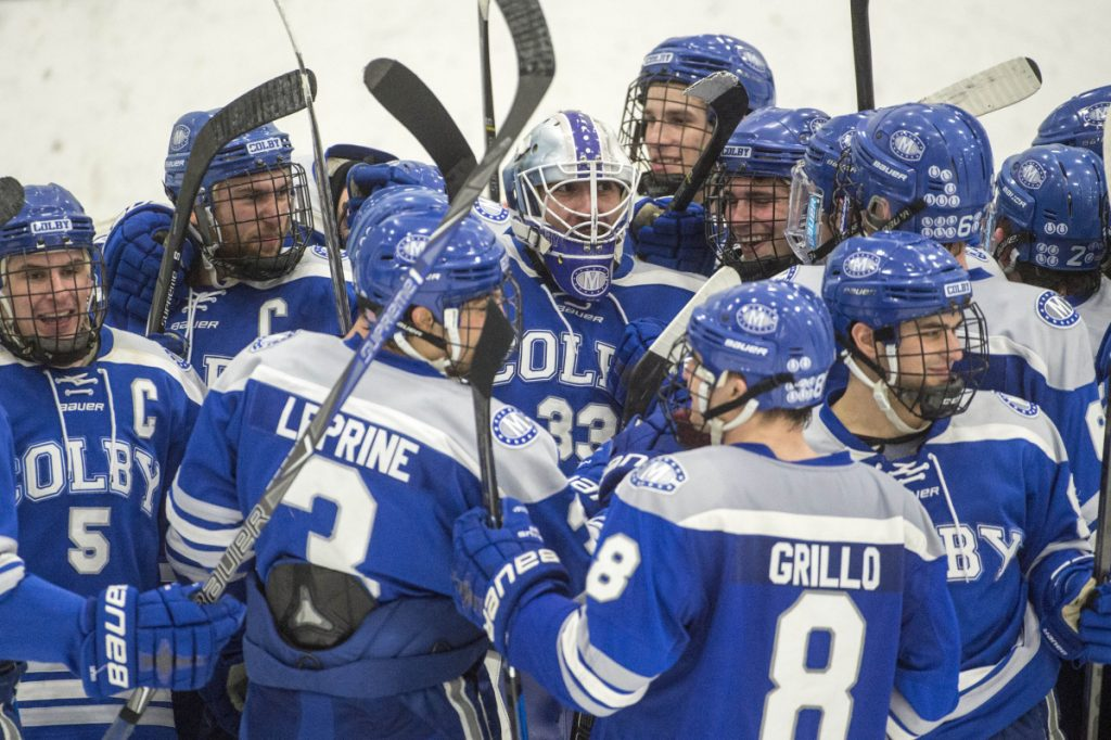 The Colby College hockey team mobs goalie Sean Lawrence after its 4-2 win over the University of New England in the first round of the NCAA Division III men's hockey tournament on Saturday in Biddeford.