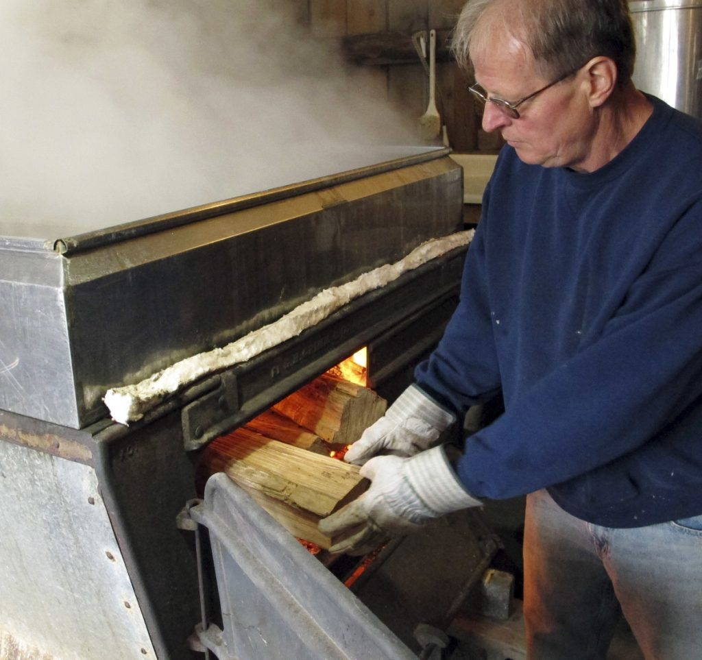 Doug Bragg of Bragg Farm Sugarhouse & Gift Shop in East Montpelier, Vt., loads firewood into an evaporator where he boils maple sap. Maple syrup season started early this year.
